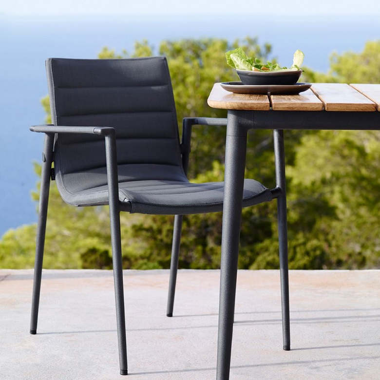 Core dining armchair by Cane-line next to a table