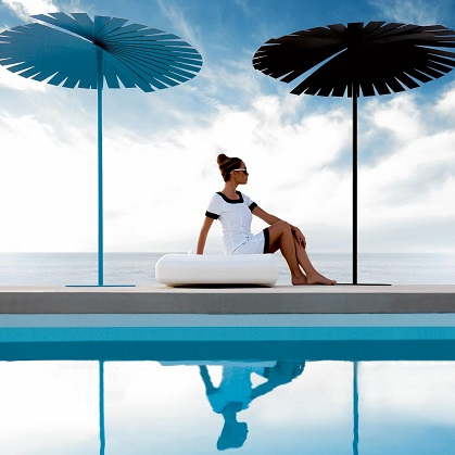 One blue and one black parasol with female sat posing in between next to infinity pool, with oceanview in background