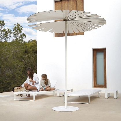 Mother, daughter and dog on a sunlounger next to a white parasol