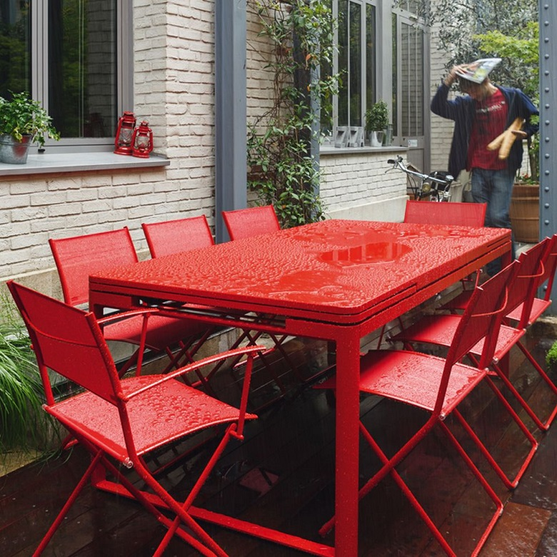 Red Biarritz dining table by Fermob outside in a garden while raining