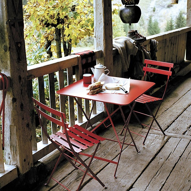 Breakfast laid out on a veranda with a red Fermob table and two chairs
