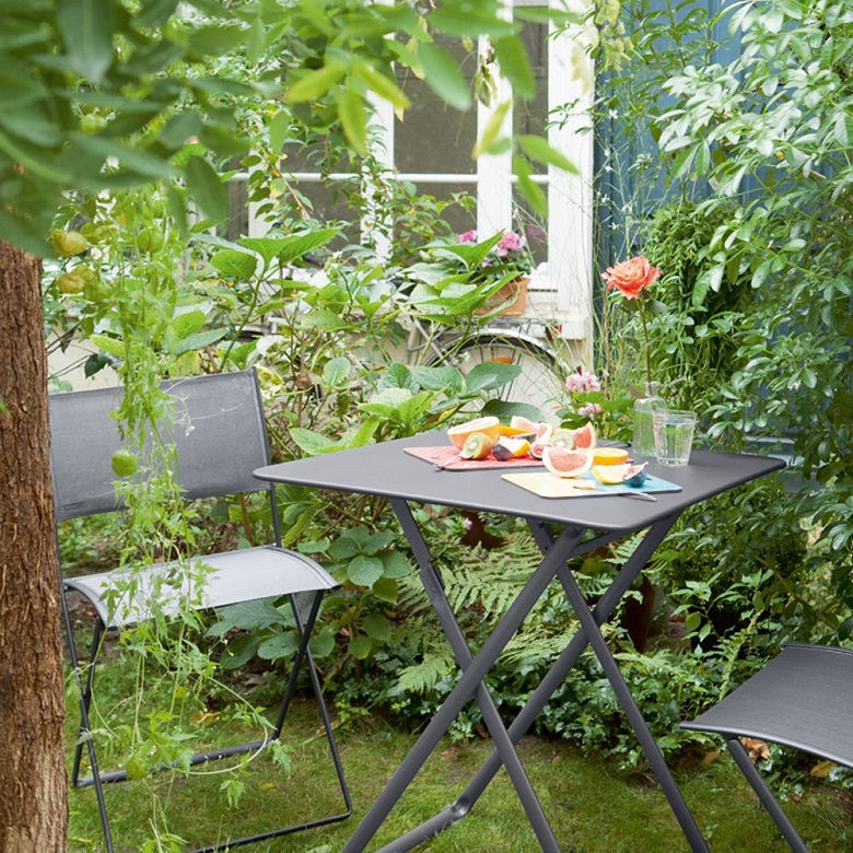 Plein Air table and chairs by Fermob in a garden
