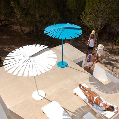 One blue and one white parasol with a female sunbathing and four people approaching from forestry