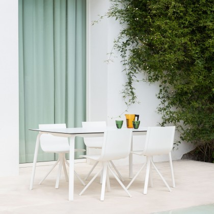 White dining table set outside on a patio