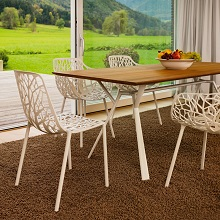 Radice quadra table with teak by Fast next to a garden setting