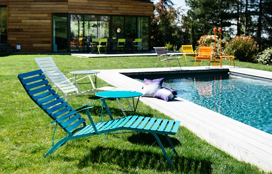 Bistro Chaise Longue sunloungers in a garden next to a swimming pool