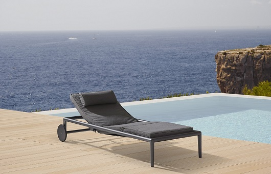 Conic outdoor sunbed next to a swimming pool with oceanview in the background