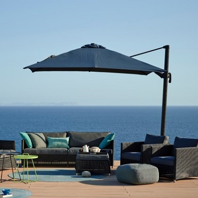 The Hyde hanging parasol by Cane-Line, with outdoor furniture and an oceanview background